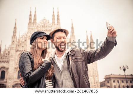 Happy tourists taking a self portrait with phone in front of Duomo cathedral,Milan - Couple traveling in Italy - stock photo