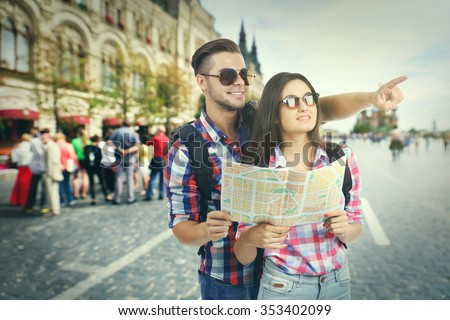 Happy tourists with map on street in city - stock photo