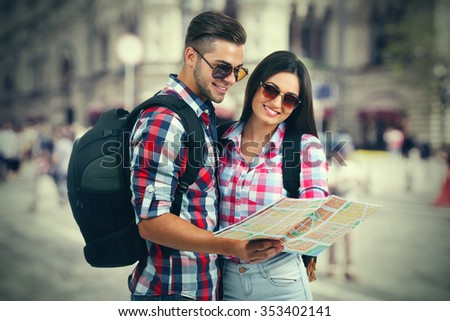 Happy tourists with map, outdoors - stock photo
