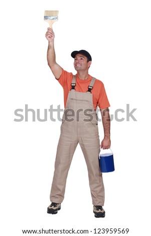 Happy tradesman painting a wall - stock photo