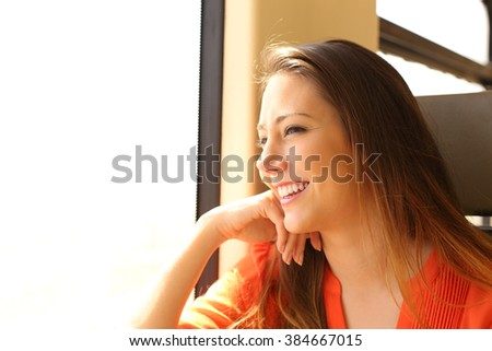 Happy train passenger traveling sitting in a seat and looking through the window - stock photo