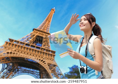 Happy travel woman in Paris with Eiffel Tower and she look map, asian beauty - stock photo