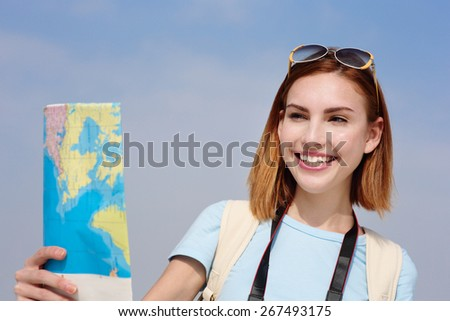 Happy travel woman look map with sky background, caucasian beauty - stock photo