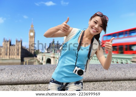 Happy travel woman show thumb up in London with Big Ben tower,  London, UK,  asian beauty - stock photo
