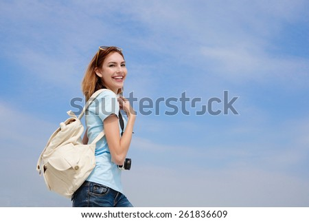 Happy travel woman smile to you with sky background, caucasian beauty - stock photo