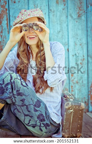 Happy traveler looking in binoculars happy smiling. toned vintage style. focus on face - stock photo