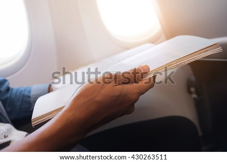 happy traveler reading a magazine in an airplane,  - stock photo
