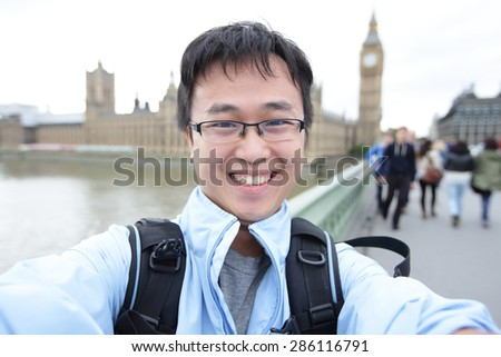 Happy traveler take photo selfie by camera in London with Big Ben tower, London, UK, asian man - stock photo