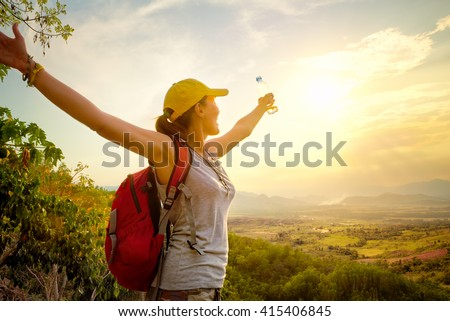 Happy traveler with backpack and bottle of water standing on top of mountain and enjoying valley view with raised hands. Mountains landscape, travel to Asia, happiness emotion, summer holiday concept - stock photo