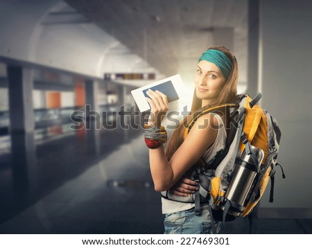 Happy traveler woman is waiting for a flight - stock photo
