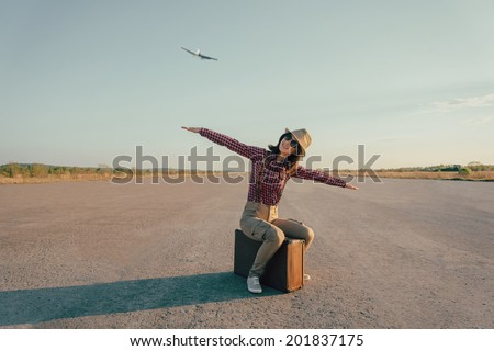 Happy traveler woman sits on vintage suitcase on road and makes a gesture of flight. With vintage retro instagram filter - stock photo