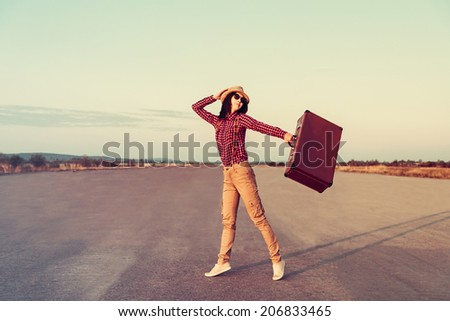 Happy traveler young woman dancing with a vintage suitcase on the road. With vintage filter - stock photo