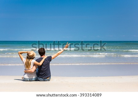 Happy travelers, man and woman, admiring perfect weather on a tropical vacation