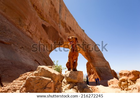 happy traveling dog sitting on a rock in the front of a sandstone arch in Utah  - stock photo