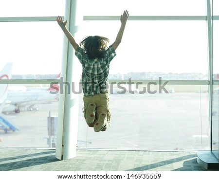Happy traveller boy jumping on airport waiting for airplane