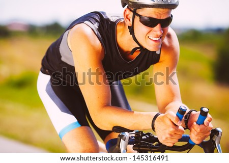 Happy triathlete cycling on a bicycle - stock photo