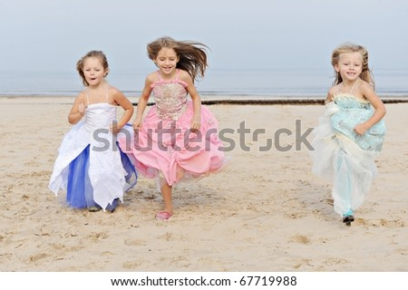 Happy tthree little girls have fun and joy time at beautiful beach while running from joy
