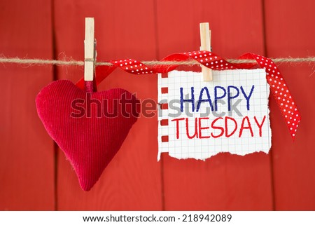 Happy Tuesday on instant paper and small red heart hanging on the clothesline. On red wood background - stock photo