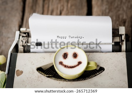 Happy Tuesday on typewriter with happy face coffee cup, sepia tone. - stock photo