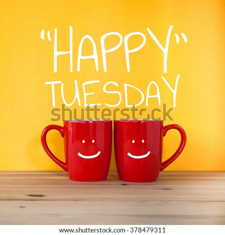 Happy Tuesday word.Two cups of coffee and stand together to be heart shape on yellow background with smile face on cup. - stock photo