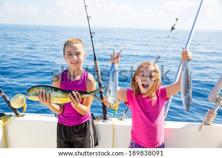 Happy tuna fisherwomen kid girls on boat with fishes trolling catch with dorado Mahi - stock photo