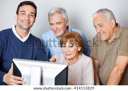 Happy Tutor Assisting Senior People In Using Computer At Class