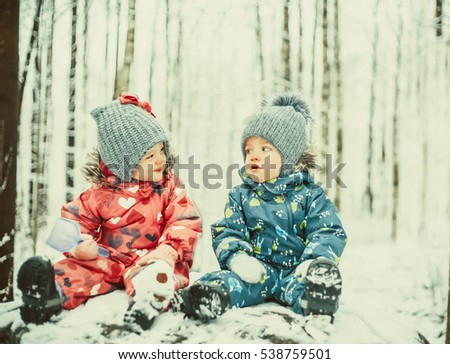 Happy twin kids boy and girl in winter snowy park