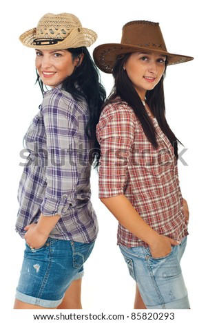 Happy two cowgirls standing back to back and wearing hats isolate don white background