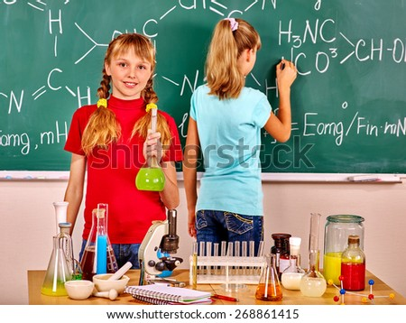 Happy two  female children  holding flask in chemistry class. - stock photo