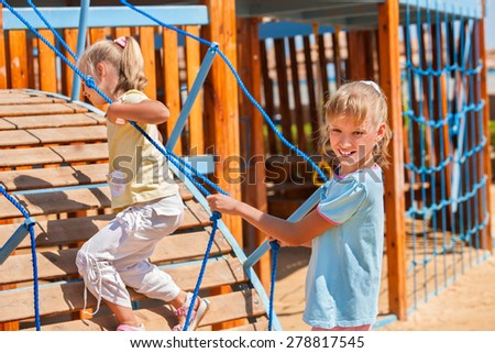 Happy two female children move out to slide in playground. - stock photo