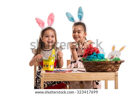 Happy two girls decorating Easter eggs isolated on white background - stock photo