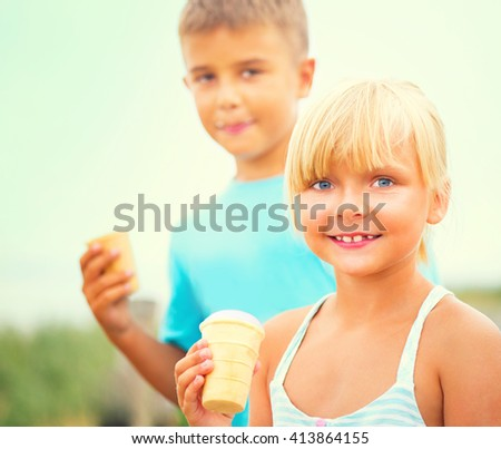 Happy two kids eating ice cream and smiling, outdoors. Children with ice-cream cone walking together and enjoying icecream in summer park