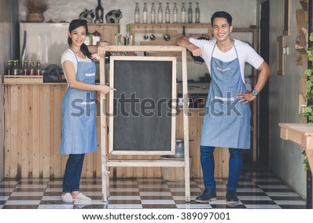 happy two small business owner ready to open their cafe. standing with blank board - stock photo