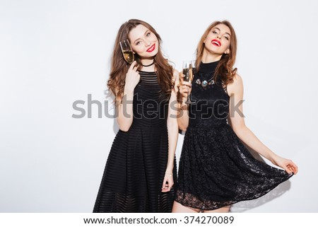 Happy two women in black dress holding glass with champagne isolated on a white background - stock photo