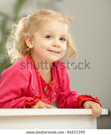 Happy two-year-old leaning on counter smiling. - stock photo