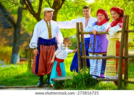 happy ukrainian family in traditional costumes together in spring garden - stock photo