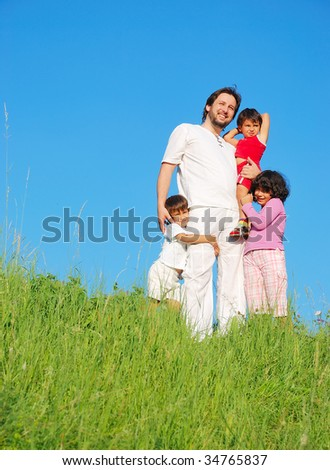 Happy unforgettable childhood on green meadow against blue sky - stock photo