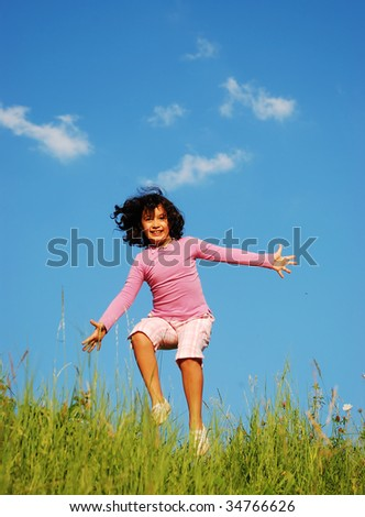 Happy unforgettable childhood on green meadow against blue sky