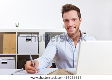 Happy university student learning with laptop and taking notes - stock photo
