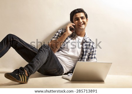 Happy university student sitting by laptop while on call