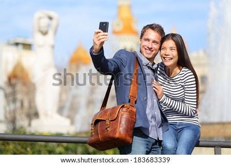 Happy urban city couple on travel in Barcelona taking selfie self portrait photograph with smart phone camera. Happy young man and woman on Placa de Catalunya, Catalonia Square, Barcelona, Spain. - stock photo