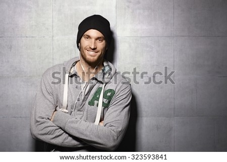 Happy urban man listening to music through earbuds, leaning against grey wall. - stock photo