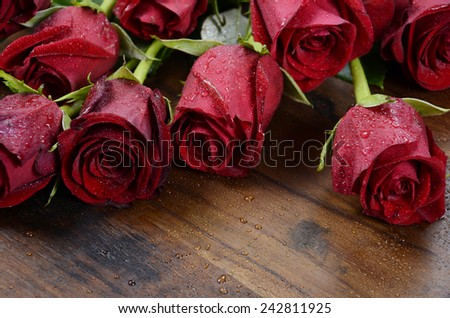 Happy Valentine's Day red roses on dark recycled wood background - closeup. - stock photo