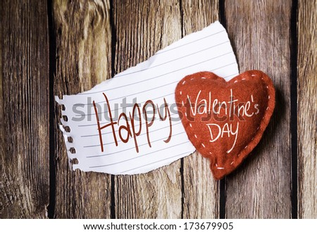 Happy Valentine's Day written on a peace of paper and a heart on a wooden background - stock photo