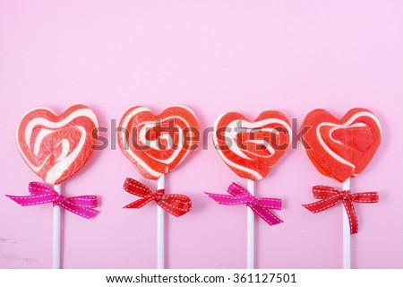 Happy Valentines Day candy with red heart shape lollipops on pink wood background. - stock photo
