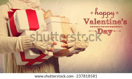 Happy Valentines Day message with woman holding present boxes - stock photo