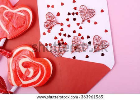 Happy Valentines Day opened love letter envelope  with red heart shape lollipop on pink wood background.
