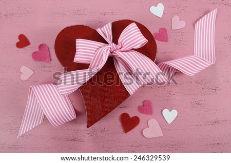 Happy Valentines Day red heart shape gift box on shabby chic vintage style pink wood table background. - stock photo