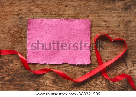 Happy Valentines Day. Red Ribbon Heart and pink paper on a wooden background. Valentines Day concept - stock photo
