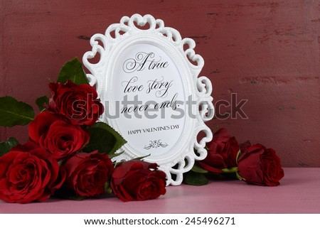 Happy Valentines Day romantic vintage style white photo frame against red and pink rustic wood background with bouquet of red roses, with A True Love Story Never Ends sample text. - stock photo